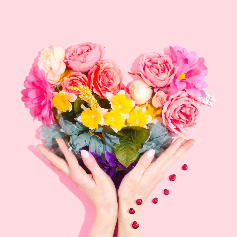 Hands holding heart shape made of a flower bouquet