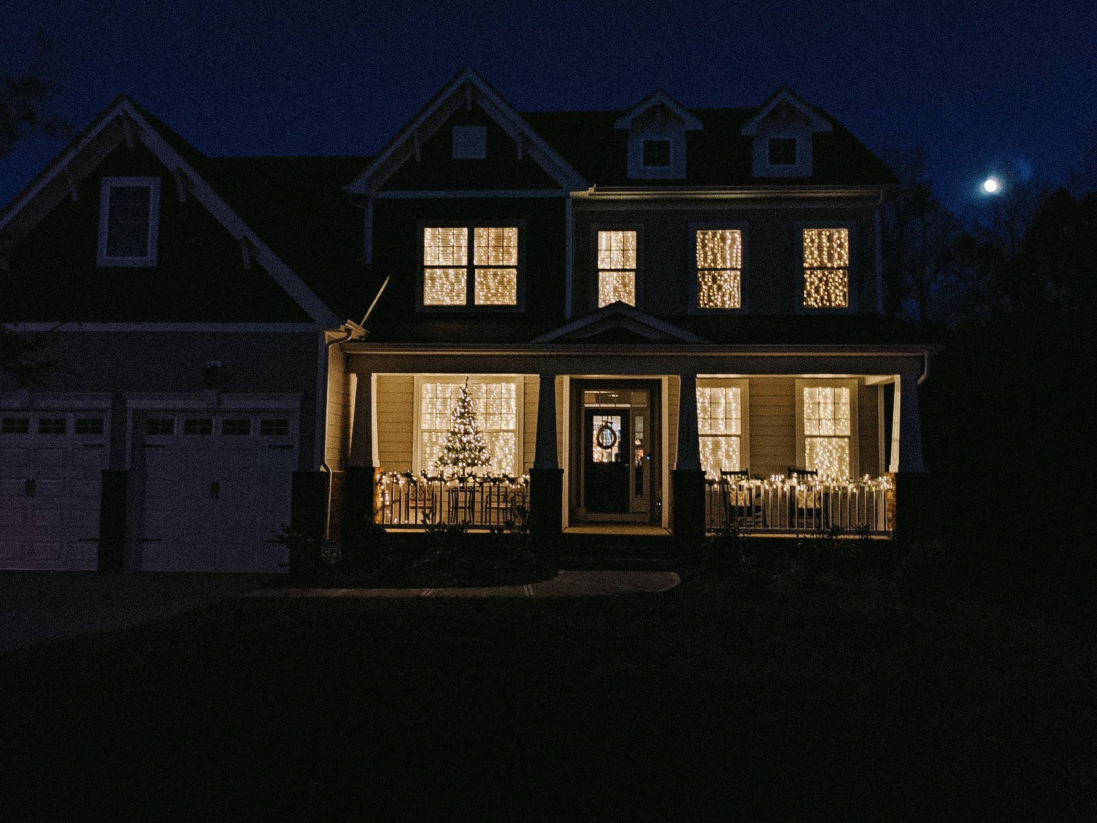 Exterior photo of two story house.Windows are filled and illuminated with Christmas lights
