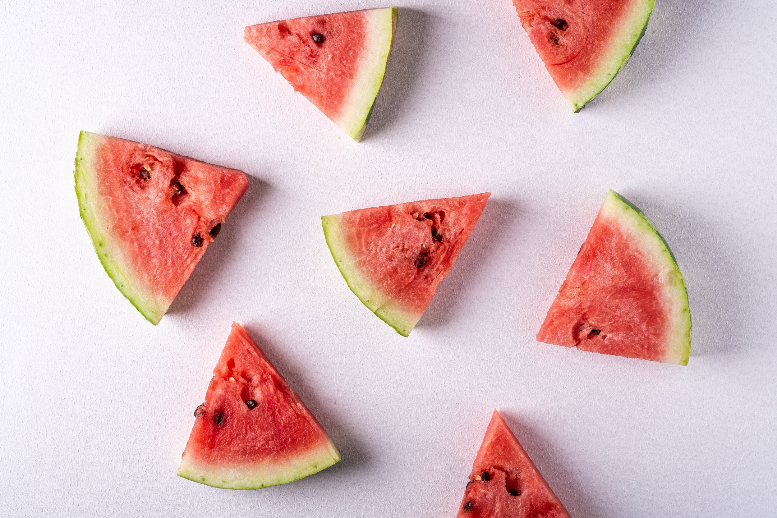Wedges of watermelon lay on top of a pink background